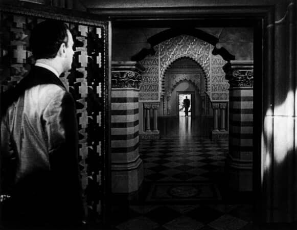 Full shot of Orson Welles as Charles Foster Kane silhouetted at other end of long hallway and Paul Stewart as Raymond in foreground looking in his direction.