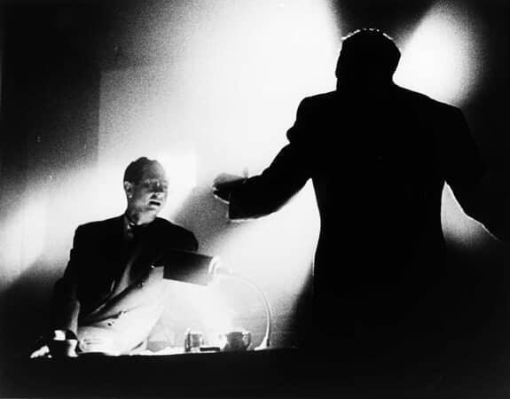 Medium shot of William Alland as Jerry Thompson seated on desk behind Philip Van Zandt as Rawlston.