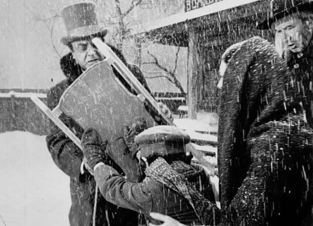 Medium shot of Buddy Swan as Young Charles Foster Kane pushing snow sled onto George Coulouris as Walter Parks Thatcher while Agnes Moorehead as Mrs. Mary Kane and Harry Shannon as Kane, Sr. observe.