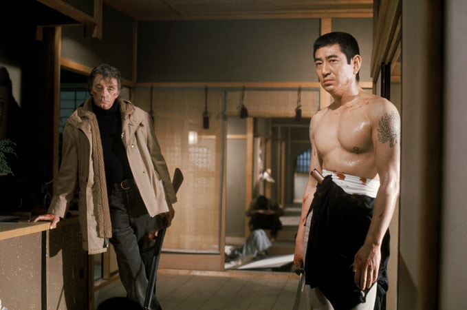 Robert Mitchum as Harry Kilmer, holding shotgun, and shirtless Takakura Ken as Ken Tanaka, holding sword.