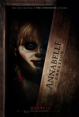 "Annabelle doll peering out of a wooden box with ""Annabelle Creation"" stamped on it"
