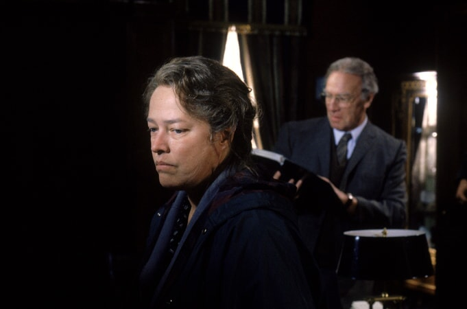 Kathy Bates as Dolores Claiborne and Christopher Plummer as Detective John Mackey, standing in background reading book.