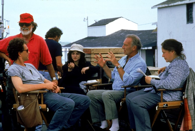 Full BTS shot of director Taylor Hackford, wearing hat/baseball cap and sunglasses, Jennifer Jason Leigh as Selena St. George, Christopher Plummer as Detective John Mackey, and Kathy Bates as Dolores Claiborne.
