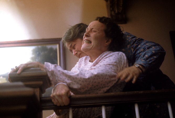 Medium shot of Kathy Bates as Dolores Claiborne holding grimacing Judy Parfitt as Vera Donovan from behind.