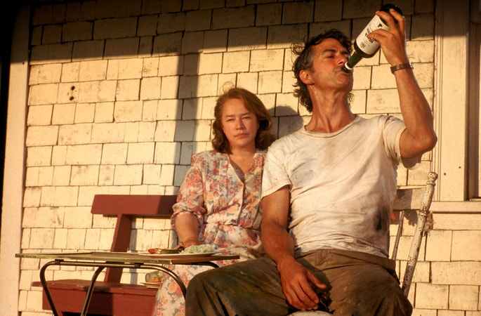 Kathy Bates as Dolores Claiborne and David Strathairn as Joe St. George, drinking from bottle of liquor; both seated on porch.