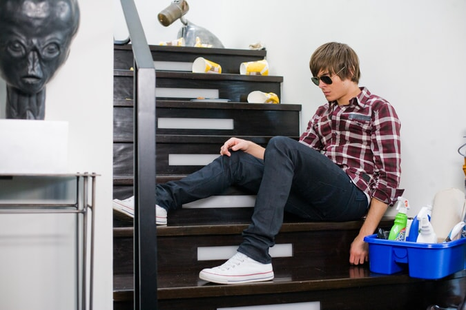 Full shot of Zac Efron as Mike O'Donnell seated on stairs wearing sunglasses