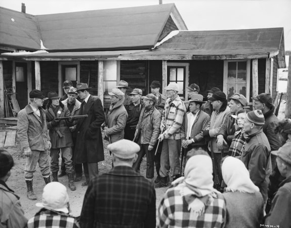 Ward Bond as Walter Brent and Ian Wolfe as Sheriff Carrey talking to Robert Ryan as townspeople look on.