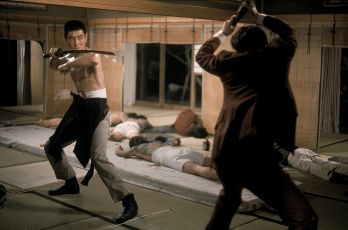 shirtless Takakura Ken as Ken Tanaka, holding sword in the yakuza