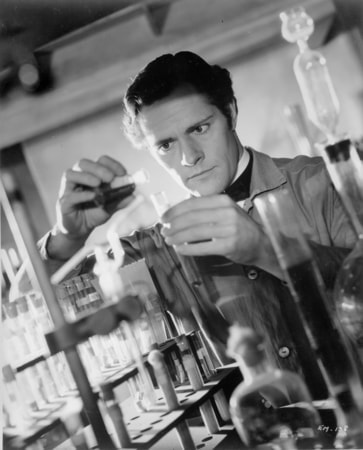 Donald Woods as Dr. Jean Martel, working in chemistry laboratory.