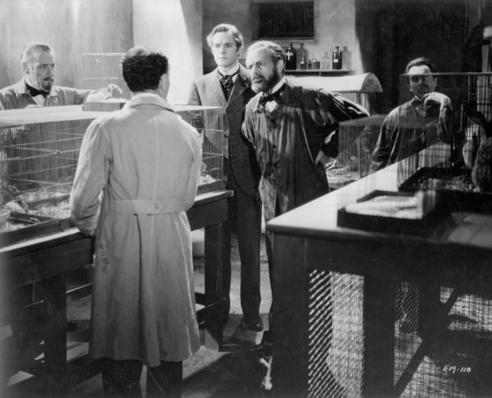 Full shot of Paul Muni as Louis Pasteur, Donald Woods as Dr. Jean Martel, and Henry O'Neill as Dr. Emile Roux facing Raymond Brown as Dr. Radisse (back to camera).