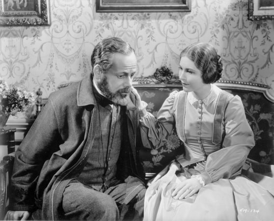 Paul Muni as Louis Pasteur and Josephine Hutchinson as Marie Pasteur, both seated.