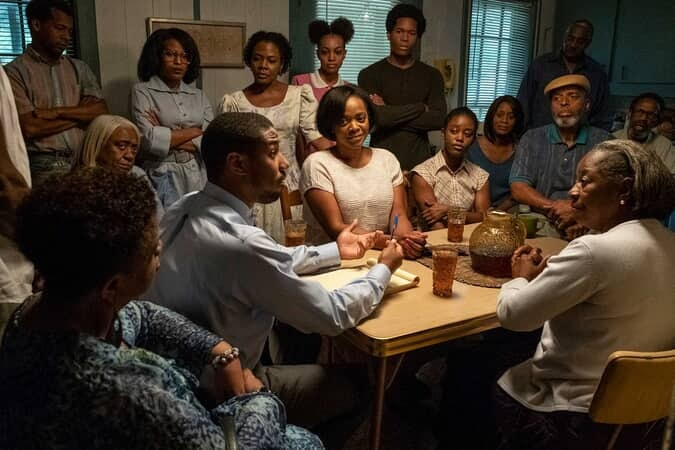 MICHAEL B. JORDAN as Bryan Stevenson and (seated to Michael's left) KARAN KENDRICK AS Minnie McMillian in Warner Bros. Pictures' drama JUST MERCY