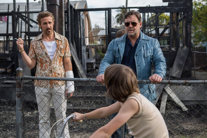 RYAN GOSLING as Holland March and RUSSELL CROWE as Jackson Healy talking to a boy on a bike in a burned out construction area