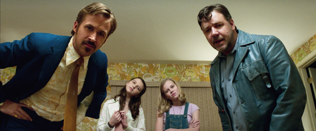 RYAN GOSLING as Holland March, DAISY TAHAN as Jessica, ANGOURIE RICE as Holly and RUSSELL CROWE as Jackson Healy all looking down at something