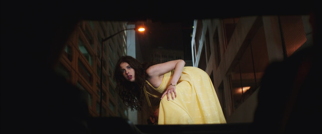 MARGARET QUALLEY as Amelia Kuttner crouching in a yellow dress