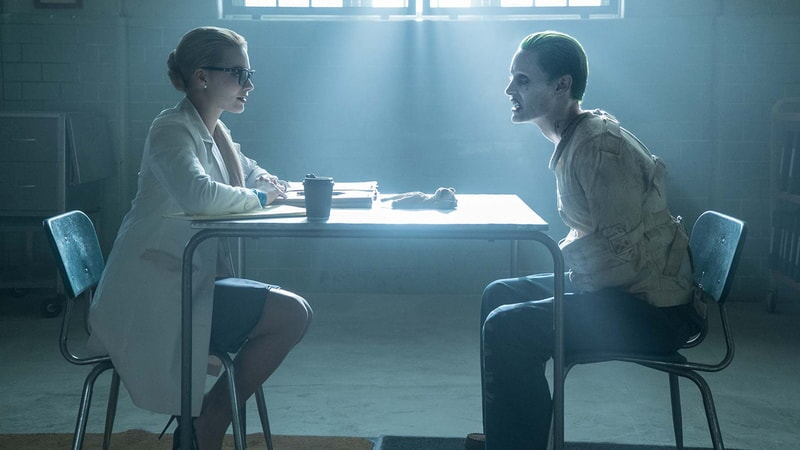 The joker wearing a strait jacket and meeting with Dr. Harleen Quinzel