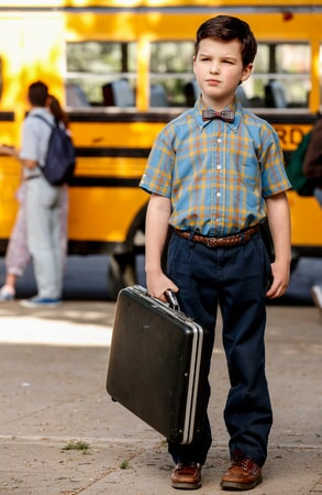 Iain Armitage wearing bowtie and a holding a briefcase from the pilot Young Sheldon episode.