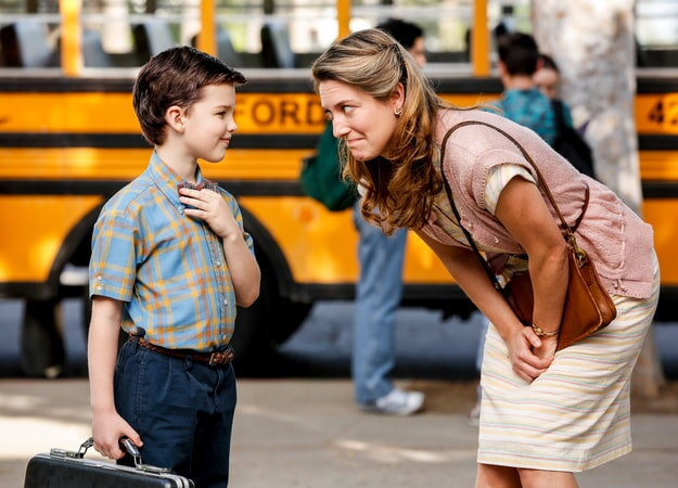 Zoe Perry and Iain Armitage standing in front a school bus in the pilot Young Sheldon episode.