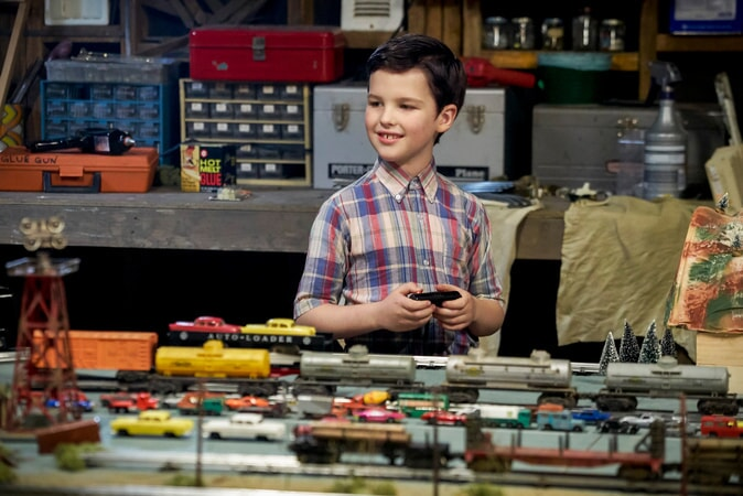 Iain Armitage in a garage with toy train sets and vintage toy cars from the pilot Young Sheldon episode.