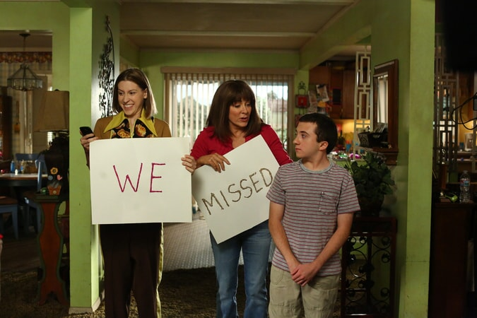 """Eden Sher, Patricia Heaton and Atticus Shaffer holding cardboard signs that say """"We"""" """"Missed"""" in Season 9, Epsiode 1 """"Vive Le Hecks"""""""