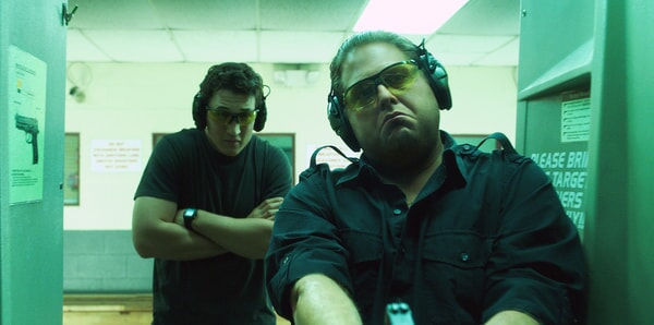 MILES TELLER as David and JONAH HILL as Efraim at indoor shooting range