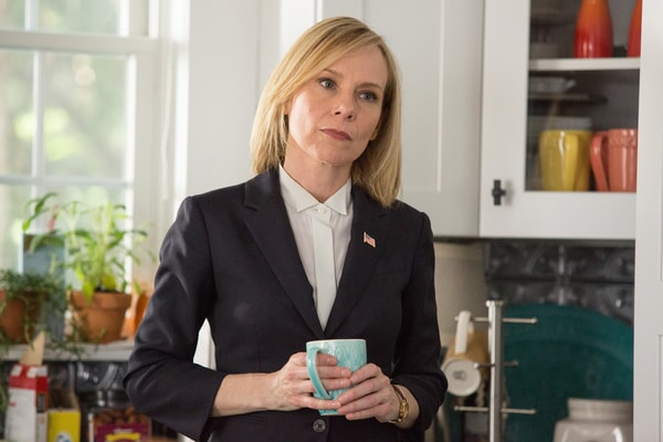 AMY RYAN as Agent Pamela Harris in a dark suit holding a coffee cup