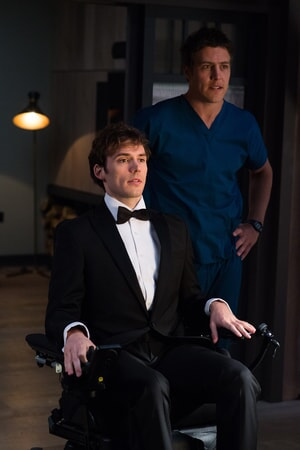 SAM CLAFLIN as Will Traynor wearing a tuxedo, sitting in wheelchair and STEPHEN PEACOCKE as Nathan wearing hospital scrubs, standing behind him.