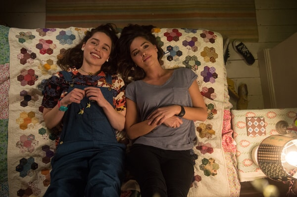 EMILIA CLARKE as Lou Clark and JENNA COLEMAN as Katrina Clark lying in bed, looking at the ceiling and smiling.