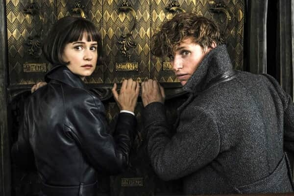 Katherine Waterston and Eddie Redmayne as Tina and Newt looking behind them
