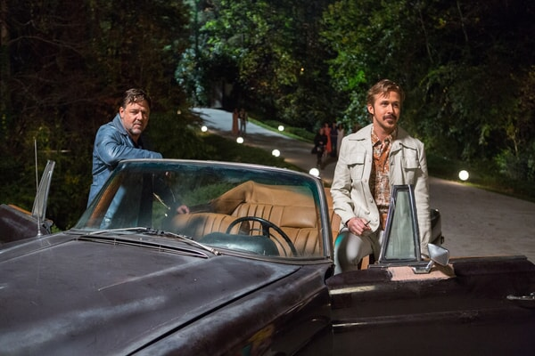 RUSSELL CROWE as Jackson Healy and RYAN GOSLING as Holland March in leisure suits standing next to a brown convertible