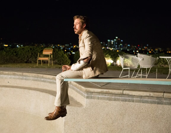 RYAN GOSLING as Holland March sitting on the edge of an empty pool