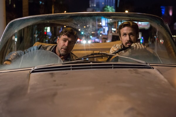 RYAN GOSLING as Holland March driving a convertible at night and RUSSELL CROWE as Jackson Healy in the passenger seat