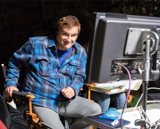 Writer/director SHANE BLACK sitting in director's chair on the set of The Nice Guys