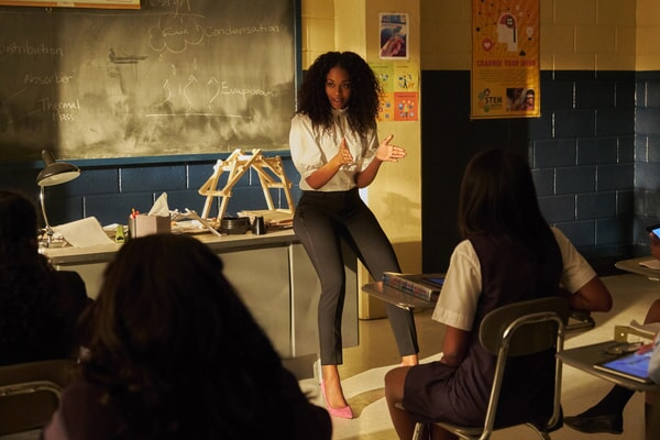 "Nafessa Williams in Episode ""Dark Matter of My Brain"" sitting on desk in classroom"